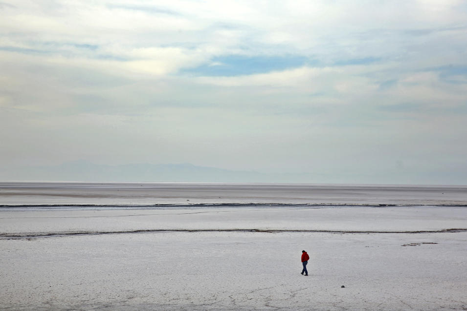 In this Saturday, Feb. 15, 2014 photo, a man walks on solidified salts at Lake Oroumieh, northwestern Iran. Oroumieh, one of the biggest saltwater lakes on Earth, has shrunk more than 80 percent to 1,000 square kilometers (nearly 400 square miles) in the past decade, mainly because of climate change, expanded irrigation for surrounding farms and the damming of rivers that feed the body of water, experts say. (AP Photo/Ebrahim Noroozi)