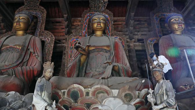 Seorang ahli konservasi peninggalan sejarah merestorasi patung tanah liat yang dicat warna di Biara Fengguo, Yixian, Jinzhou, Provinsi Liaoning, China (8/6/2020). Dibangun pada 1020, Biara Fengguo menjadi rumah bagi koleksi langka patung tanah liat Buddha yang dicat warna. (Xinhua/Yao Jianfeng)