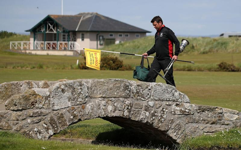 Greenkeeper Simon Connah crosses the Swilcan Bridge on the Old Course at St Andrews, in Fife as final preparations are completed to the course ahead of reopening - PA