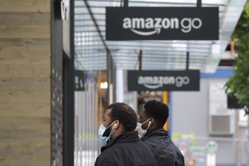 Two people wearing masks walk near an Amazon Go store, Thursday, April 30, 2020, in downtown Seattle. Amazon.com is expected to announce earnings for the first quarter of 2020 at the close of markets Thursday, a report that is expected to be closely watched due to the effects of the coronavirus outbreak on the company. (AP Photo/Ted S. Warren)