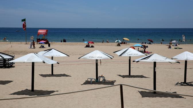 Para pengunjung menerapkan aturan jaga jarak sosial saat menikmati sinar matahari di Pantai Carcavelos, di Lisbon, Portugal (6/6/2020). (Xinhua/Petro Fiuza)