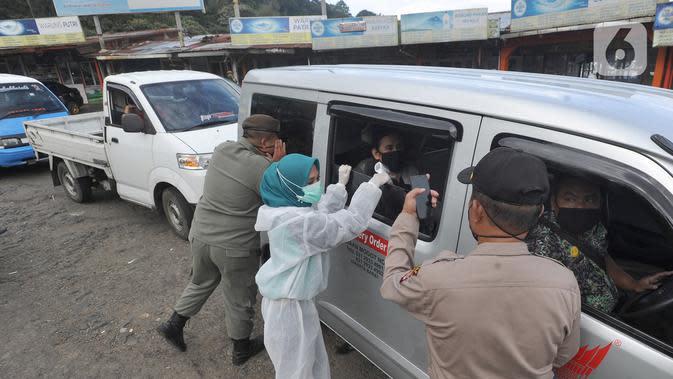 Petugas memeriksa surat keterangan lolos uji rapid test pada warga yang akan melakukan perjalanan di Pos Pam Puncak Pass, Cianjur, Minggu (17/5/2020). Mereka diperbolehkan melakukan perjalanan kecuali dilengkapi surat tugas atau surat keterangan sehat dari pihak berwenang. (merdeka.com/Arie Basuki)
