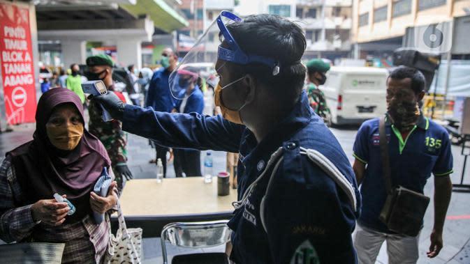 Petugas mengecek suhu pengunjung sebelum memasuki Pasar Tanah Abang Blok A, Jakarta, Senin (15/6/2020). Setelah hampir tiga bulan ditutup, kawasan Pasar Tanah Abang kembali beroperasi pada Senin (15/6) diikuti dengan penerapan protokol kesehatan pencegahan Covid-19. (Liputan6.com/Faizal Fanani)