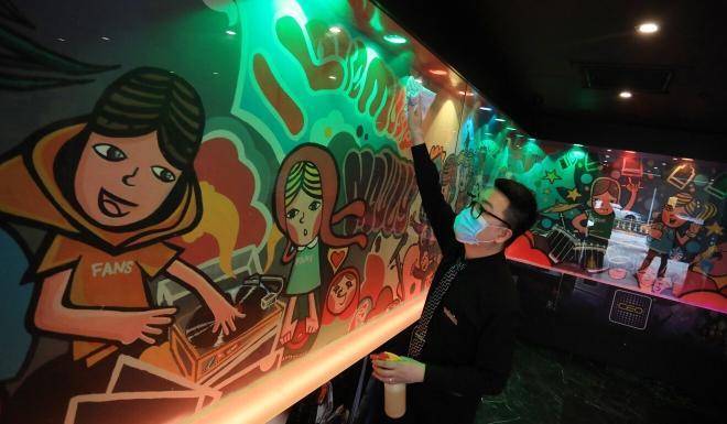 A staff member disinfects a karaoke lounge in Tsim Sha Tsui. Photo: May Tse