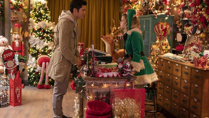 Henry Golding dan Emilia Clarke di toko milik Santa. (Foto: Dok. IMDb/ Universal Pictures)