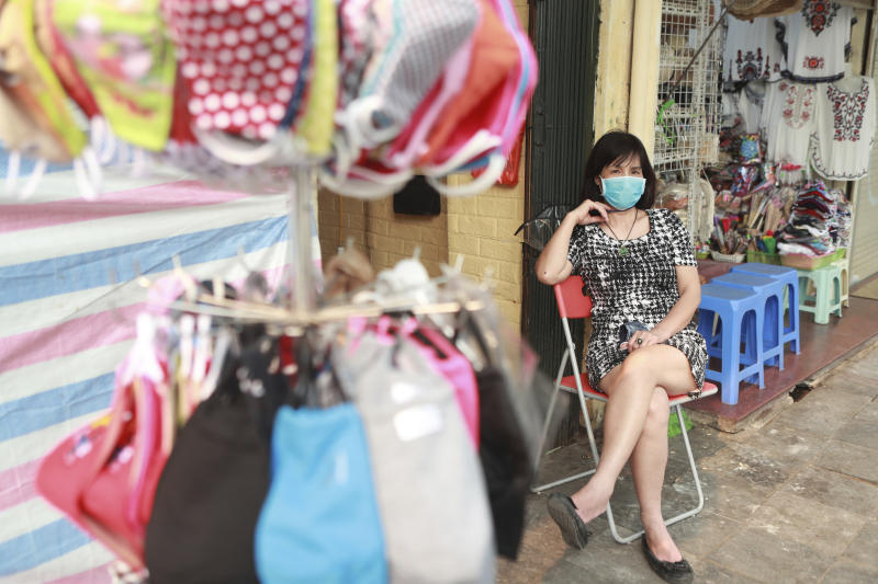 Shop owner Kim Anh sits next to a pole hanger of face masks for sale in Hanoi, Vietnam, Friday, March 27, 2020. Vietnam's Prime Minister Nguyen Xuan Phuc has ordered to shut down non-essential business to curb the spread of COVID-19. The new coronavirus causes mild or moderate symptoms for most people, but for some, especially older adults and people with existing health problems, it can cause more severe illness or death. (AP Photo/Hau Dinh)
