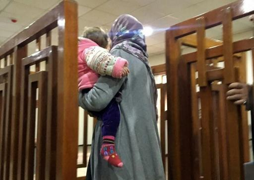 File photo taken on February 19, 2018, of French citizen Melina Boughedir carrying her son as she arrives to court in the Iraqi capital Baghdad where on June 3, 2018 she was sentenced to life in jail for membership of the Islamic State group