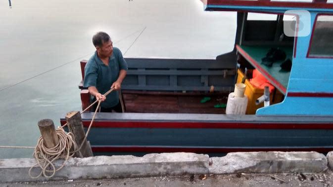 Perahu-perahu nelayan ditambatkan di pantai yang berfungsi sebagai dermaga nelayan. Mereka tak berani melaut karena ombak dan gelombang tinggi. (foto: Liputan6.com/ajang nurdin)