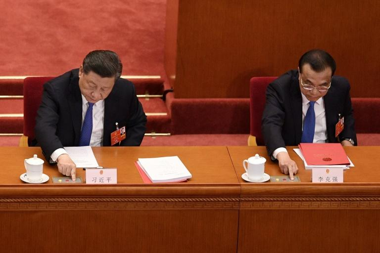 China's President Xi Jinping (left) and Premier Li Keqiang vote on a proposal to draft a Hong Kong security law during the closing session of the National People's Congress at the Great Hall of the People in Beijing