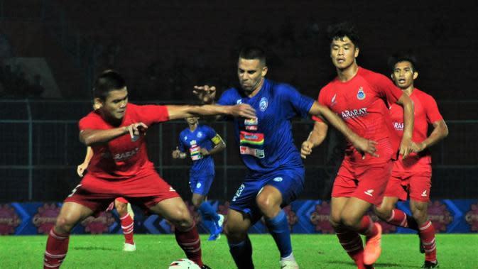 Striker Arema FC, Elias Alderete, dihadang para pemain Sabah FA pada laga lanjutan Grup B Piala Gubernur Jatim 2020 di Stadion Kanjuruhan, Kabupaten Malang, Selasa (11/2/2020) malam WIB. Dalam laga itu, Arema menang 2-0. (Bola.com/Iwan Setiawan)