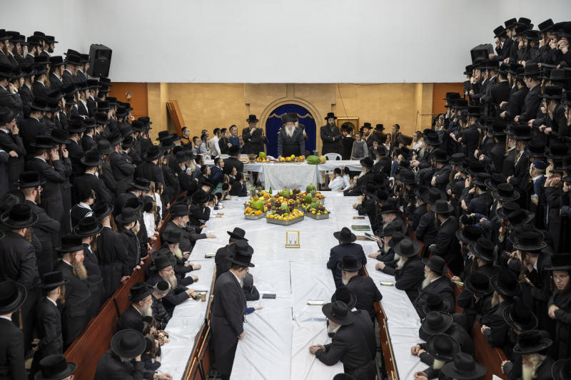 """Ultra-Orthodox Jews of the Nadvorna Hasidic dynasty celebrate the Jewish feast of 'Tu Bishvat' or """"New Year of the Trees."""" as they sit with their rabbis around a long table filled with all kinds of fruits, in the ultra-Orthodox town of Bnei Brak, Israel, Monday, Feb. 10, 2020. (AP Photo/Oded Balilty)"""