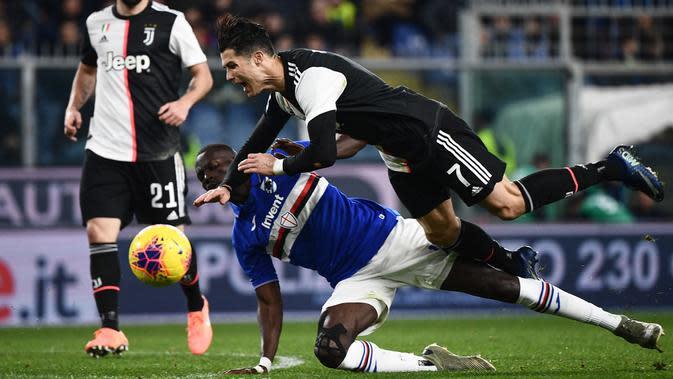 Striker Juventus, Cristiano Ronaldo, terjatuh saat berebut bola dengan bek Sampdoria, Omar Colley pada laga Serie A 2019 di Stadion Luigi Ferraris, Rabu (18/12). Juventus menang 2-1 atas Sampdoria. (AFP/Marco Bertorello)