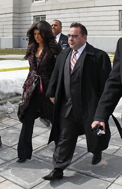 "Teresa, left, and Joe Giudice, from ""The Real Housewives of New Jersey,"" leave federal court in Newark, N.J. on Tuesday, March 4, 2014. They each pleaded guilty to several counts including bankruptcy fraud, conspiracy to commit mail fraud and wire fraud, and failing to pay taxes. (AP Photo/Rich Schultz)"