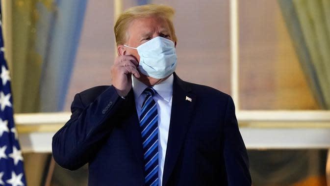Presiden AS Donald Trump melepas maskernya saat berdiri di balkon di luar Blue Room setelah kembali ke Gedung Putih, Washington, Senin (5/10/2020). Donald Trump meninggalkan Walter Reed National Military Medical Center, rumah sakit tempat dia menjalani perawatan COVID-19. (AP Photo/Alex Brandon)