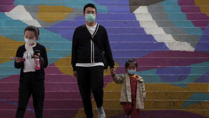 Sebuah keluarga mengenakan masker untuk mengekang penyebaran COVID-19 di Beijing, China, Minggu (11/10/2020). Meski penyebaran COVID-19 hampir diberantas di China, pandemi masih melonjak di seluruh dunia dengan jumlah kematian yang terus meningkat. (AP Photo/Andy Wong)