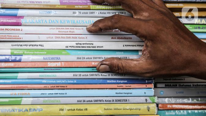 Pedagang memeriksa buku dagangannya di kawasan Kwitang Jakarta, Jumat (26/6/2020). Sejumlah pedagang mengaku penjualan buku mengalami penurunan hingga 50 persen karena imbauan Pemerintah untuk tinggal dirumah dan libur sekolah selama pandemi COVID-19. (Liputan6.com/Faizal Fanani)