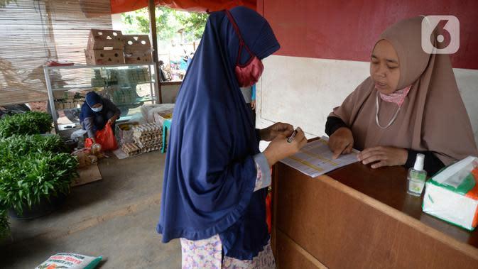 Warga yang memiliki kartu ATM Keluarga Sejahtera mengisi data saat mengambil bantuan pangan non tunai dari Kemensos di Kelurahan Buaran, Serpong, Tangerang Selatan, Banten, Jumat (16/10/2020). Bantuan pangan non tunai tersebut diterima 95 orang. (merdeka.com/Dwi Narwoko)
