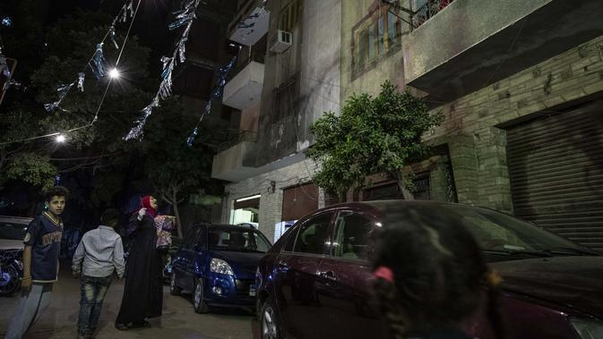 Seorang mesaharati Hajja Dalal (46) membangunkan warga untuk sahur saat bulan suci Ramadan di Kairo, Mesir, Rabu (29/4/2020). Meski telah ada teknologi alarm, namun pekerjaan sebagai mesaharati masih bertahan hingga saat ini. (AP Photo/Nariman El-Mofty)