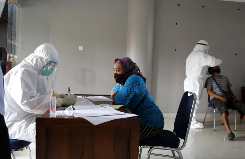 A heath worker checks ID of woman as she waits to takes a nasal swab sample during a public testing for the coronavirus conducted at a market in Bali, Indonesia on Saturday, June 6, 2020. (AP Photo/Firdia Lisnawati)