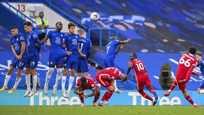 Pemain Liverpool Trent Alexander-Arnold (kanan) melakukan tendangan bebas saat menghadapi Chelsea pada pertandingan Liga Premier Inggris di Stadion Stamford Bridge, Minggu (20/9/2020). Liverpool menang 2-0 lewat gol Sadio Mane. (Michael Regan/Pool via AP)
