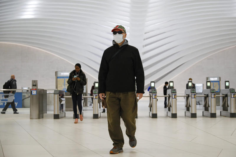 A commuter wears a face mask in the New York City transit system, Monday, March 9, 2020, in New York. New York continued grappling Monday with the new coronavirus, as case numbers, school closings and other consequences grew. (AP Photo/John Minchillo)