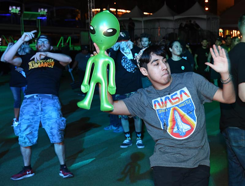 """LAS VEGAS, NEVADA - SEPTEMBER 19: Dany Pinelo of Nevada wears a tin foil hat as he dances with an inflatable alien during the Area 51 Celebration at the Downtown Las Vegas Events Center on September 19, 2019 in Las Vegas, Nevada. The event is one of several in Nevada being held as a result of a Facebook event entitled, """"Storm Area 51, They Can't Stop All of Us,"""" suggesting people storm the highly classified U.S. Air Force facility at the Nevada Test and Training Range to address a conspiracy theory that the U.S. government is conducting tests with space aliens, went viral. Matty Roberts said he created the event as a joke. (Photo by Ethan Miller/Getty Images)"""