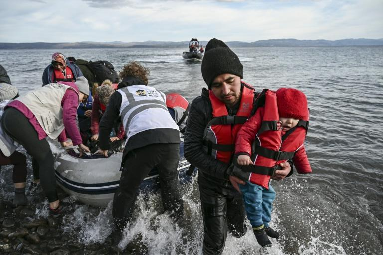 NGO members help refugees disembark from a dinghy as it lands on the Greek island of Lesbos