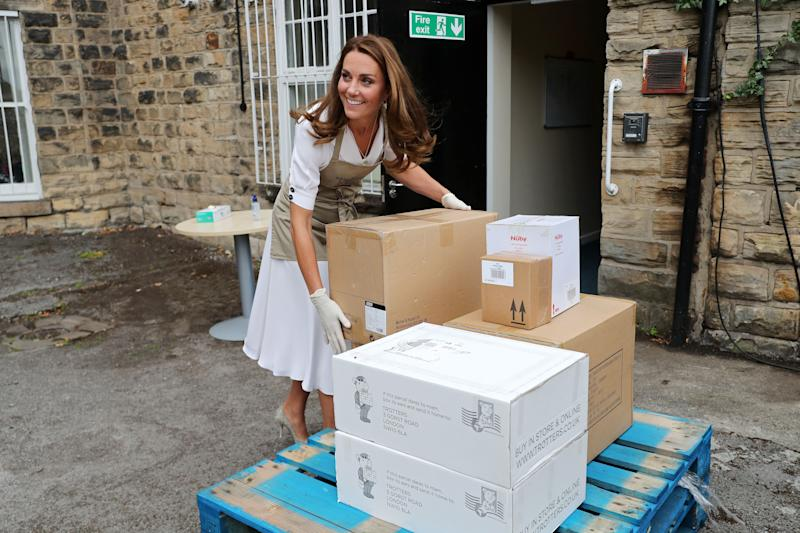 Britain's Catherine, Duchess of Cambridge wears gloves and an apron as she helps to unpack supplies during her visit to Baby Basics baby bank in Sheffield, northern England on August 4, 2020. - Baby banks aim to support and empower families by ensuring every child has the essential items they need to thrive. In the UK, they are powered primarily by volunteers and typically run on professional referral from services such as health visitors, midwives and social workers. (Photo by Chris Jackson / POOL / AFP) (Photo by CHRIS JACKSON/POOL/AFP via Getty Images)