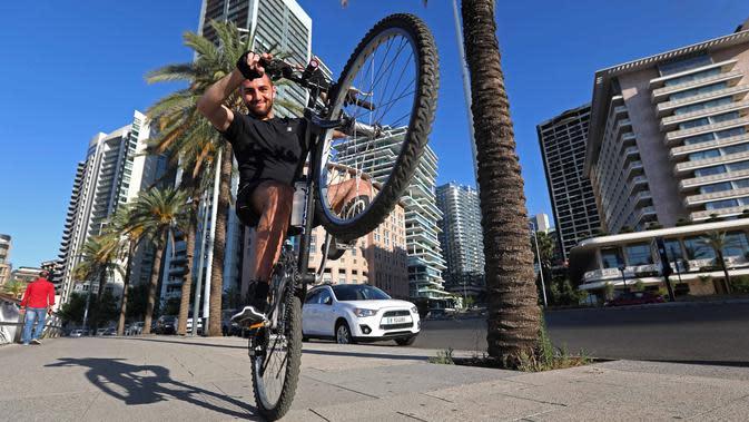 Seorang pria memamerkan kepiawaiannya beratraksi di atas sepeda di Beirut, Lebanon (11/6/2020). Belakangan ini, kegiatan bersepeda menjadi aktivitas yang lazim di Lebanon sejak pemerintah memberlakukan pembatasan guna meredam pandemi COVID-19. (Xinhua/Bilal Jawich)