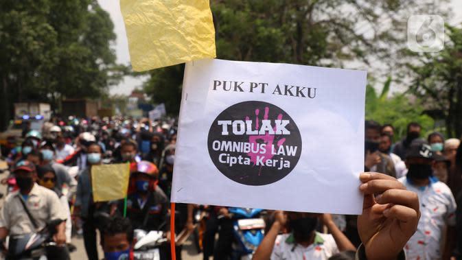 Buruh membawa spanduk saat melakukan aksi di Kota Tangerang, Banten, Selasa (6/10/2020). Dalam aksi tersebut mereka menolak UU Omnibus Law Cipta Kerja yang sudah disahkan oleh DPR RI. (Liputan6.com/Angga Yuniar)