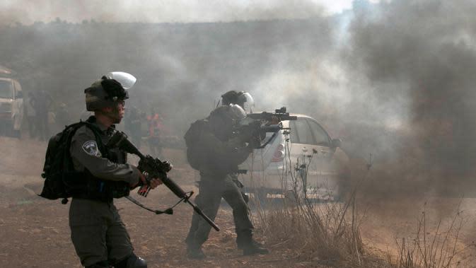 Pasukan penjaga perbatasan Israel membidik saat bentrok dengan pengunjuk rasa Palestina di Ramallah, Tepi Barat, Kamis (17/10/2019). Pengunjuk rasa menentang pembangunan pos terdepan Israel di dekat desa Palestina, Turmus Ayya, dan pemukiman Israel, Shilo. (JAAFAR ASHTIYEH/AFP)