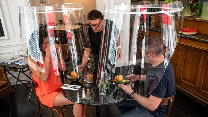 Sejumlah orang berpose di bawah purwarupa gelembung plexiglass Plex'Eat di restoran H.A.N.D di Paris, pada 27 Mei 2020. Plex'Eat dapat disesuaikan dengan semua jenis tempat usaha dan butik serta tempat-tempat umum untuk melindungi para tamu selama pandemi COVID-19. (Xinhua/Aurelien Morissard)