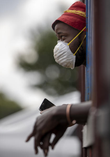 A man wearing a face mask to protect against coronavirus, watches the South African National Defence Forces raids a hostel in densely populated Alexandra township east of Johannesburg, South Africa, Saturday, March 28, 2020. South Africa went into a nationwide lockdown for 21 days in an effort to mitigate the spread to the coronavirus.The new coronavirus causes mild or moderate symptoms for most people, but for some, especially older adults and people with existing health problems, it can cause more severe illness or death. (AP Photo/Themba Hadebe)
