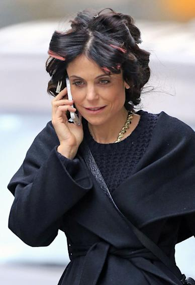 Bethenny Frankel heads out with curlers in her hair and chats on the phone while after leaving her apartment in New York City