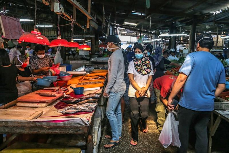 Customers do their shopping at the Gunung Rapat wet market in Kuala Lumpur March 26, 2020. — Picture by Firdaus Latif