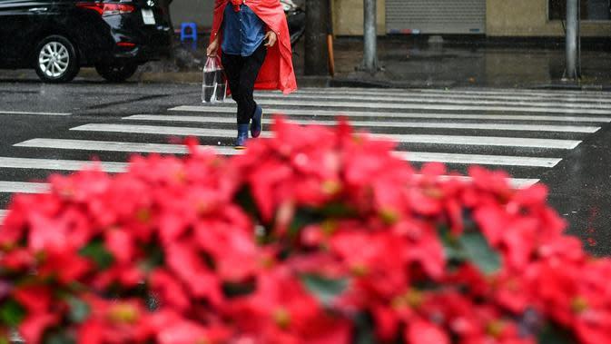 Seorang wanita menyeberang jalan saat hujan deras di Hanoi (14/10/2020). Badai tropis Nangka menghantam Vietnam tengah-utara yang mengakibatkan bencana alam, terutama hujan lebat dan banjir, telah menyebabkan 28 orang tewas dan 12 lainnya hilang. (AFP Photo/Manan Vatsyayana)
