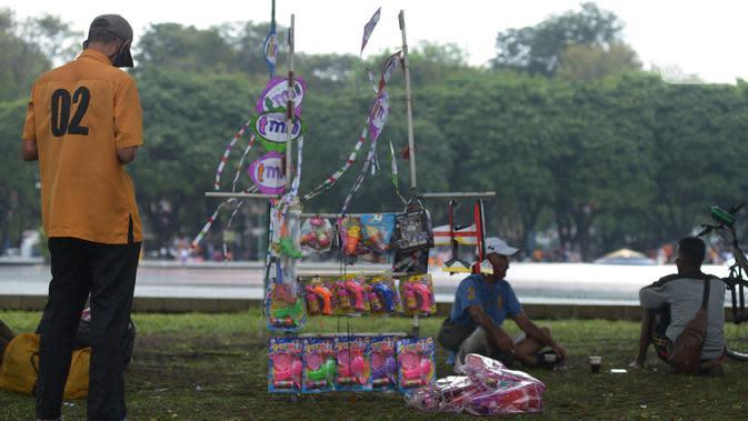 Pedagang menjual dagangan di Taman Mini Indonesia Indah, Jakarta, Kamis (20/8/2020). Warga memanfaatkan momen libur panjang Tahun Baru islam 1442 H ke tempat rekreasi yang dekat karena masih situasi pandemi Corona (COVID-19) dengan menjaga protokol kesehatan. (merdeka.com/Imam Buhori)