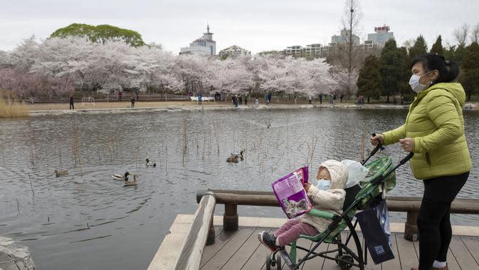 Seorang wanita membawa bayi saat menikmati bunga sakura di Taman Yuyuantan, Beijing, China, Kamis (26/3/2020). Musim semi dan bunga sakura bermekaran memikat warga untuk keluar rumah dari yang sebelumnya membatasi diri karena pandemi virus corona COVID-19. (AP Photo/Ng Han Guan)