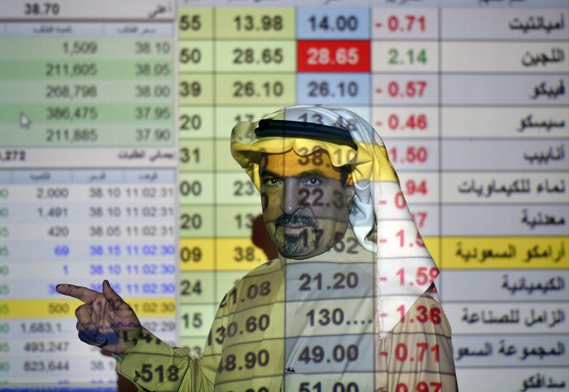 """FILE- In this Thursday, Dec. 12, 2019, file photo, a trader talks to others in front of a screen displaying Saudi stock market values at the Arab National Bank in Riyadh, Saudi Arabia. Saudi Arabian oil company Aramco's initial public offering raised $29.4 billion, more than previously announced after the company said Sunday it used a so-called """"greenshoe option"""" to sell an additional 450 million shares to satiate investor demand. (AP Photo/Amr Nabil, File)"""