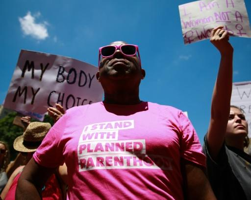 """A man wears an """"I stand with Planned Parenthood"""" shirt at a protest against recently passed abortion ban bills at the Georgia State Capitol building, on May 21, 2019 in Atlanta"""