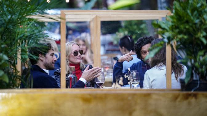 Pengunjung duduk di luar restoran yang menawarkan layanan area luar ruangan (outdoor) di New York pada 3 Oktober 2020. Kota itu mengizinkan restoran membuat area makan outdoor hingga ke trotoar dan jalanan sebagai upaya mengatasi dampak ekonomi COVID-19 yang berkelanjutan. (AP Photo/John Minchillo)