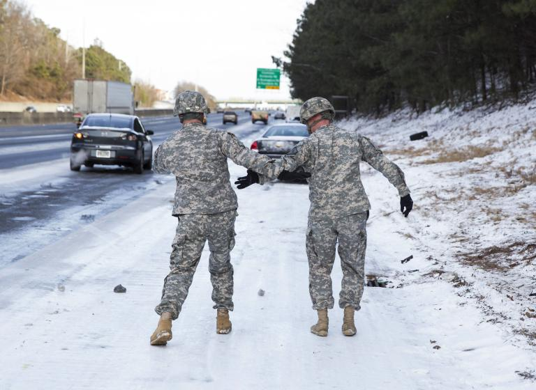 Georgia National Guard troops help each other from slipping on the ice as they assist people in getting their stranded cars in Atlanta, Georgia