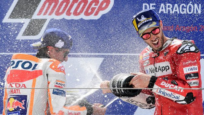 Pembalap Ducati, Andrea Dovizioso (kanan), berselebrasi dengan Marc Marquez setelah balapan MotoGP Aragon, Minggu (22/9/2019). (AFP/Javier Soriano)