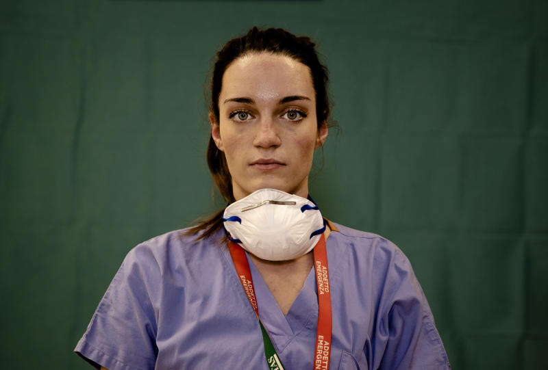 Martina Papponetti, 25, an ICU nurse at the Humanitas Gavazzeni Hospital in Bergamo, Italy poses for a portrait at the end of her shift Friday, March 27, 2020. Their eyes are tired. Their cheekbones rubbed raw from protective masks. They don't smile. The doctors and nurses on the front lines of the coronavirus pandemic in Italy are almost unrecognizable behind their masks, scrubs, gloves and hairnets - the flimsy battle armor donned at the start of each shift as the only barrier to contagion. (AP Photo/Antonio Calanni)