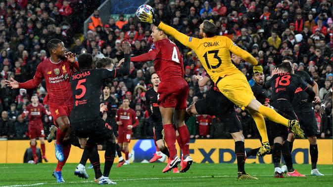 Kiper Atletico Madrid, Jan Oblak berusaha menipis bola sundulan bek Liverpool Virgil van Dijk pada kedua 16 besar Liga Champions di Anfield, Inggris (11/3/2020). Oblak melakukan sembilan penyelamatan dipertandingan ini dan membawa atletico ke perempat final. (AFP/Paul Ellis)