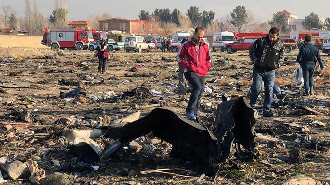 Orang-orang berjalan di antara puing-puing setelah pesawat Boeing 737 jatuh di dekat Bandara Internasional, Teheran, Iran, Rabu (8/1/2020). Seluruh penumpang pesawat maskapai Ukraina yang membawa 176 orang termasuk kru tersebut dilaporkan tewas. (AFP Photo)