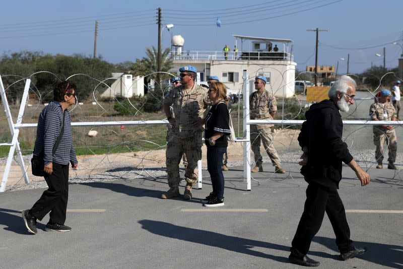 FILE PHOTO: UN Peacekeepers watch people crossing a newly opened checkpoint in Dherinia