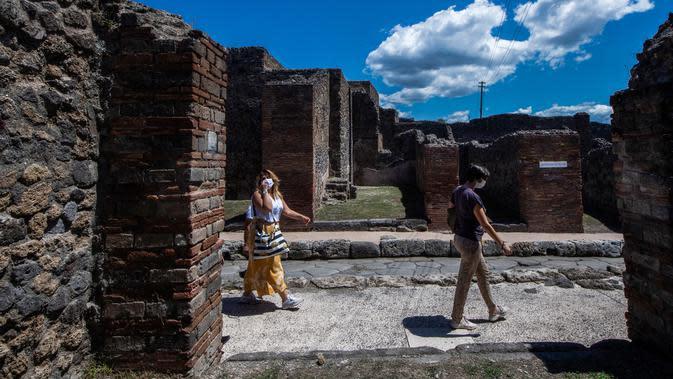 Orang-orang mengunjungi situs arkeologi Pompeii seusai kebijakan lockdown selama dua bulan untuk mengendalikan penyebaran Covid-19 di Italia, Selasa (26/5/2020). Salah satu situs arkeologi paling terkenal di dunia ini dibuka kembali untuk umum pada 26 Mei. (Tiziana FABI / AFP)