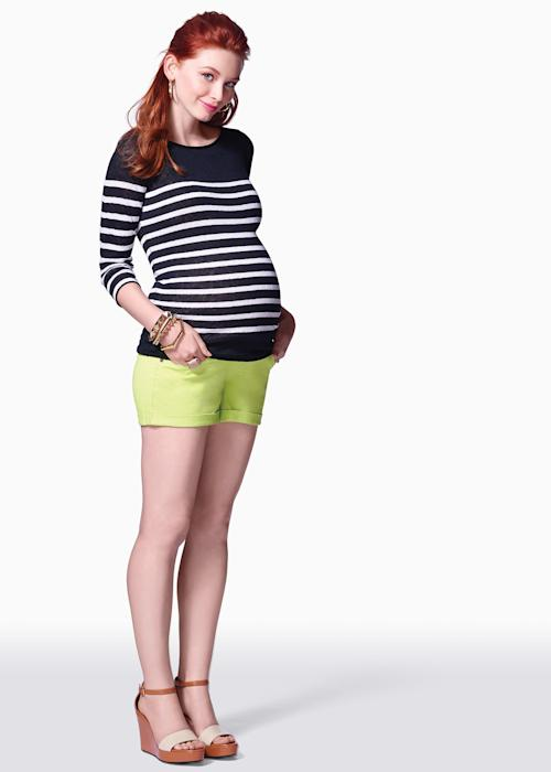 This product image released by maternity clothing company Pea in the Pod shows a model sporting shorts and a black and white striped top. Fashion experts say a streamlined style best suits a baby bump. (AP Photo/Pea in the Pod)