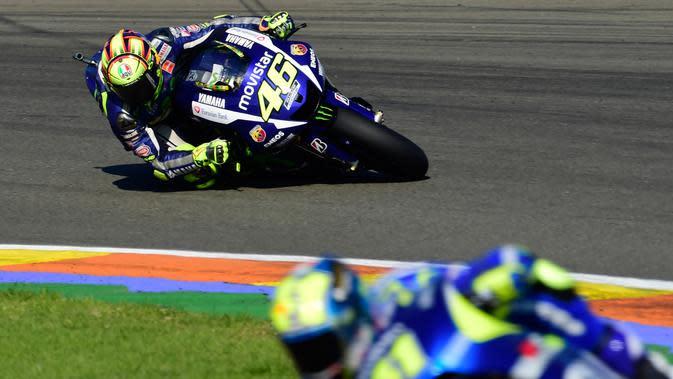Pembalap Yamaha, Valentino Rossi berusaha menyalip pembalap Suzuki, Aleix Espargaro di lintas balap Moto GP di grand Prix Valencia di Circuit Ricardo Tormo, Valencia, Minggu (8/11). (AFP PHOTO / JAVIER Soriano)